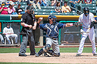 Peter O'Brien (23) of the Reno Aces and home plate umpire Ryan Blakney in action against the Salt Lake Bees in Pacific Coast League action at Smith's Ballpark on May 10, 2015 in Salt Lake City, Utah.  Salt Lake defeated Reno 9-2 in Game One of the double-header. (Stephen Smith/Four Seam Images)