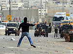 Palestinian youth throws stones at Israeli soldiers during the clashes at the Qalandia checkpoint between the West Bank city of Ramallah and Jerusalem on March 17, 2010. Israel on Wednesday lifted its tight restrictions on Palestinian access to Jerusalem's holiest shrine and called off an extended West Bank closure after days of clashes between Palestinians and Israeli security forces. While there were no reports of new clashes in Jerusalem, sporadic violence broke out Wednesday in the West Bank. Photo by Issam Rimawi