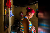A Salvadoran sex worker stands in the door of a room where her sexual services are offered to clients in San Salvador, El Salvador, 21 February 2014. Although prostitution is not legal in El Salvador, dozens of street sex workers, wearing provocative miniskirts, hang out in the dirty streets close to the capital's historic center. Sex workers of all ages are seen on the streets but a significant part of them are single mothers abandoned by their male partners. Due to the absence of state social programs, they often seek solutions to their economic problems in sex work. The environment of street sex business is strongly competitive and dangerous, closely tied to the criminal networks (street gangs) that demand extortion payments. Therefore, sex workers employ any tool at their disposal to struggle hard, either with their fellow workers, with violent clients or with gang members who operate in the harsh world of street prostitution.