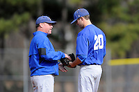 Head coach Tim Wallace of the Spartanburg Methodist College Pioneers, left, hands the ball to reliever Michael Wright (20) in a junior college game against Lenoir Community College on February 2, 2014, at Mooneyham Field in Spartanburg, South Carolina. SMC won 23-8. (Tom Priddy/Four Seam Images)