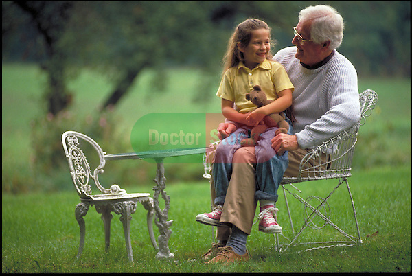 young girl sitting on grandfather's lap in backyard