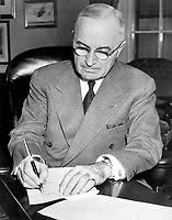 Washington (DC) USA - December 16, 1950. - <br /> US President Truman initiating Korean involvement - President Harry S. Truman is shown at his desk at the White House signing a proclamation declaring a national emergency.  December 16, 1950.