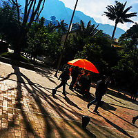 Colombian students pass along a street food cart during the sunrise in La Candelaria, Bogotá, Colombia, 24 November 2017.