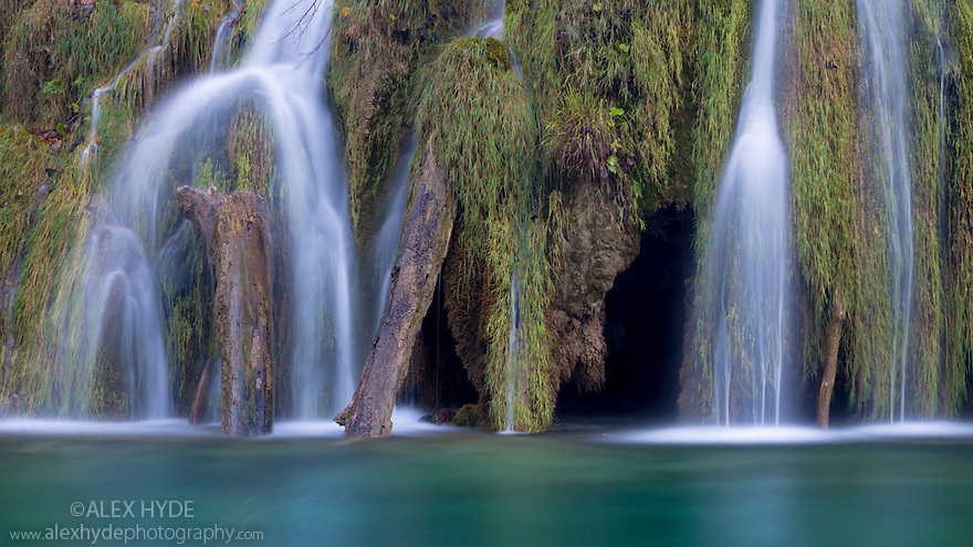 Waterall cascading over a naturally formed tufa dam. The tufa results from calcium carbonate deposits gradually accumulating on mosses and water plants, creating a solid limestone structure over time. Plitvice Lakes National Park, Croatia. November.