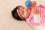 4 month old baby girl closeup on back interested in toy she is holding with one hand and touching with the other hand