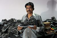 A factory worker stands with a shoe made of leather produced from the factories of Kanpur. As with much of the city's leather, it is destined for western markets.