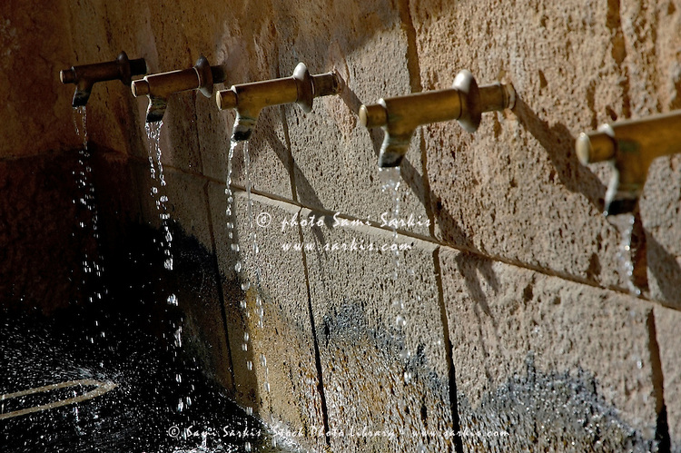 Five dripping taps along a stone wall.
