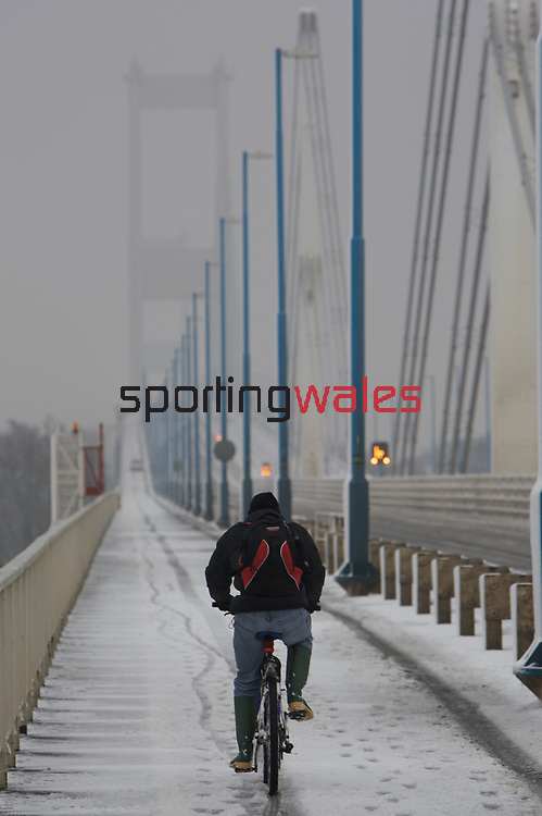 A Cyclist makes his way over the Severn Bridge in the snow.<br />
