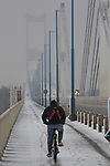 A Cyclist makes his way over the Severn Bridge in the snow.<br /> 13.01.10<br /> ©Steve Pope<br /> Sportingwales<br /> The Manor <br /> Coldra Woods<br /> Newport<br /> South Wales<br /> NP18 1HQ<br /> 07798 830089<br /> 01633 410450<br /> steve@sportingwales.com<br /> www.fotowales.com<br /> www.sportingwales.com<br /> ©Steve Pope<br /> Sportingwales<br /> The Manor <br /> Coldra Woods<br /> Newport<br /> South Wales<br /> NP18 1HQ<br /> 07798 830089<br /> 01633 410450<br /> steve@sportingwales.com<br /> www.fotowales.com<br /> www.sportingwales.com
