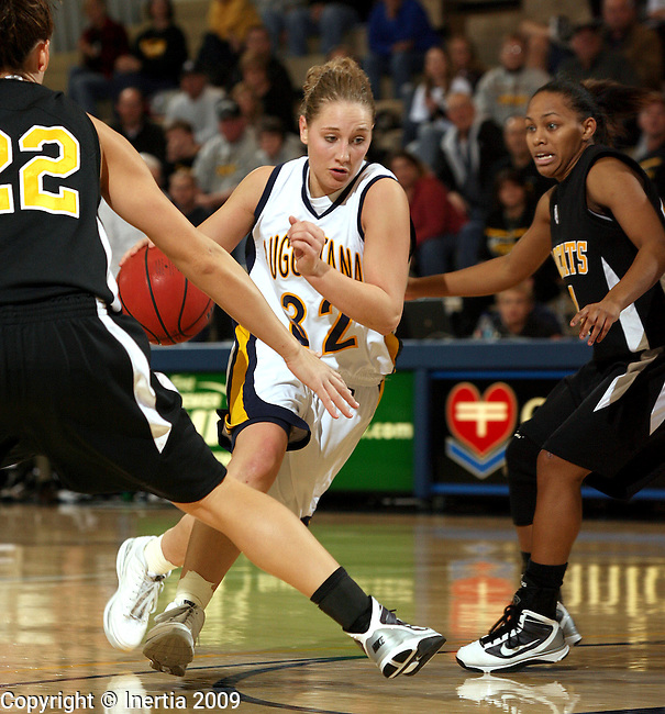 SIOUX FALLS, SD - DECEMBER 12: Megan Doyle #32 of Augustana drives the lane between Kati Jo Christensen #22 and Alisha Brown #24 from Wayne State in the second half of their game Saturday night at the Elmen Center in Sioux Falls. (Photo by Dave Eggen/Inertia)