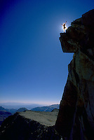 A climber silhouetted in front of the sun standing on the jagged rocky summit of Mount Conness in Yosemite National Park, California.