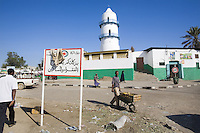 """Djibouti. Djibouti province. Djibouti. Mosque with a minaret. Black muslim people walk on the road. The sign in arabic language says: """" The poor and the needy persons will be happy with your zakat. (The zakat is an obligatory duty, the third of the five pillars of islam, and refers to spending a fixed portion of one's wealth for the poor ot the needy. )  © 2006 Didier Ruef"""