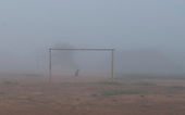 Xingu Indigenous Park, Mato Grosso State, Brazil. Aldeia Yawalapiti. A dog sits in the goal posts  in the morning mist.