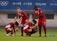 Canadian captain (12) Christine Sinclair and defender (3) Emily Zurrer are comforted by teammates (13) Amy Walsh and (5) Robyn Gayle after  playing at Shanghai Stadium.  The US defeated Canada, 2-1, in extra time and advanced to the semifinals during the 2008 Beijing Olympics in Shanghai, China.