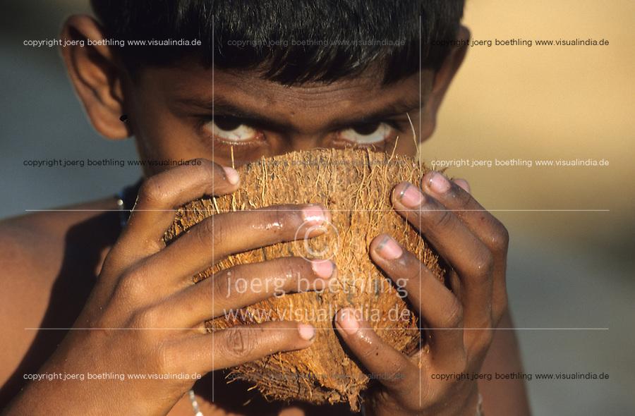 INDIEN Karnataka, Junge trinkt Kokoswasser aus Kokosnuß auf Plantage bei Mangalore / INDIA boy drink coconut water from coconut at farm near Mangalore