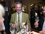 © Joel Goodman - 07973 332324 . 24/04/2014 . Knutsford , UK . UKIP leader NIGEL FARAGE on a walkabout tour of Knutsford on the European election campaign trail , shares a drink with customers in a wine bar . Farage has come under fire in recent days over a controversial UKIP billboard campaign . Photo credit : Joel Goodman