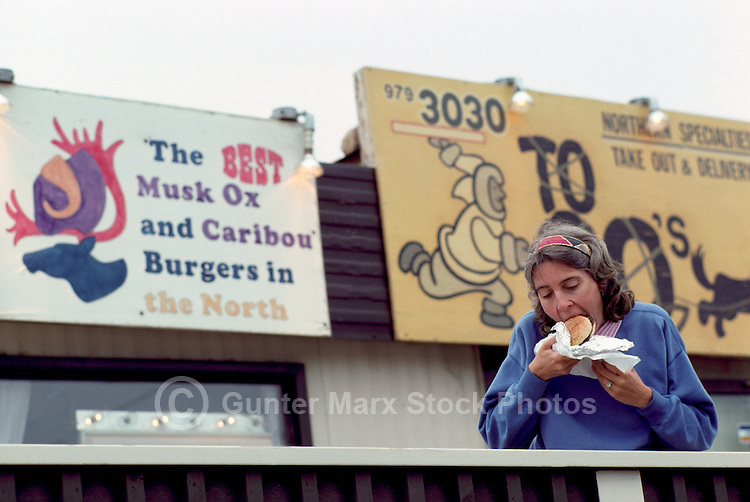 Inuvik, NWT, Northwest Territories, Arctic Canada - Tourist eating Burger at Fast Food Restaurant serving Musk Ox and Caribou Burgers (Model Released)