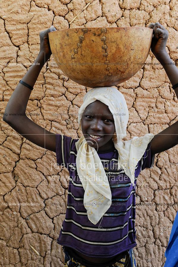 NIGER Zinder, young woman with calabass on the head in village BABAN TAPKI / NIGER Zinder, Dorf BABAN TAPKI, Caritas CADEV Projekte Ernaehrungssicherung, Familie von MARIAMA MOUSSA wird mit Nahrungsmitteln unterstuetzt