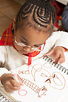 Education preschool 3-4 year olds art activity girl drawing with marker wearing eyeglasses vertical drawing letter O or circle