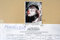 A picture of a Shahid and the Ramadan pray timetable on the door of the room transformed into a mosque in the URiC Bielany Centre in Warsaw..The picture of the Shahid (Martyr) killed by Russian Force is captioned: âHe is smiling because he sees heavenâ.