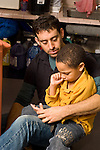 Preschool male teacher with sad or angry child on his lap talking to him