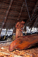 One man working on crafting a boat, city of refuge (Puu Honua o Honaunau)