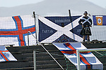 Faroe Islands 0 Scotland 2, 06/06/2007. European Championship Qualifier. A Scottish fan stands proudly in front of a selection of Scottish and Faroese flags before the Euro 2008 group B qualifying match at the Svangaskard stadium in Toftir between the Faroe Islands and Scotland. The visitors won the match by 2 goals to nil to stay in contention for a place at the European football championships which were to be held in Switzerland and Austria in the Summer of 2008. It was the first time Scotland had won in the Faroes, the previous two matches ended in draws. Photo by Colin McPherson.