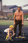 Miners strike 1984 Shirebrook Colliery Derbyshire. Striking miners scavenge for free coal in waste ground of the spoilt tip.1980s UK  Father and son, colliery in background.