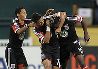 WASHINGTON, DC. - AUGUST 22, 2012:  Andy Najar (14) and Marcelo Saragosa (11) of DC United congratulate Brandon McDonald (4) after scoring against the Chicago Fire during an MLS match at RFK Stadium, in Washington DC,  on August 22. United won 4-2.