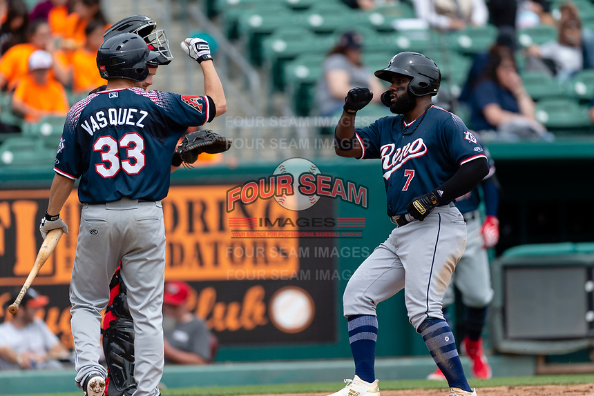 Reno Aces Abraham Almonte (7) is congratulated by Anthony Vasquez (33) after hitting a home run during a game against the Fresno Grizzlies at Chukchansi Park on April 8, 2019 in Fresno, California. Fresno defeated Reno 7-6. (Zachary Lucy/Four Seam Images)