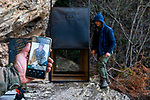 Balkan Lynx (Lynx lynx balcanicus) former hunter, Plumb Mustafa, turned conservationist holding cell phone photo during last collaring with biologist, Eko Veapi and box trap in the background, Mavrovo National Park, North Macedonia
