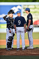 Asheville Tourists catcher Brian Serven (25), starting pitcher Riley Pint (32) and pitching coach Ryan Kibler (9) have a discussion on the mound during a game against the Augusta GreenJackets at McCormick Field on July 15, 2017 in Asheville, North Carolina. The Tourists defeated the GreenJackets 2-1. (Tony Farlow/Four Seam Images)