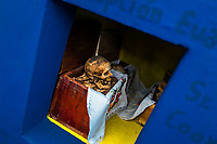 """A dried-up scull and bones are seen wrapped in a cloth and placed in a wooden crate inside a niche at the cemetery in Pomuch, Mexico, 27 October 2019. Every year on the Day of the Dead, people of Pomuch, a small Mayan community in the south of Mexico, visit the cemetery to take part in a pre-Hispanic tradition of cleaning of bones of their departed relatives (""""Limpia de huesos""""). People who die in Pomuch are firstly buried for three years in an above-ground tomb then the dried-up bodies are taken out, bones are separated, wrapped in a decorated cloth, put into a wooden crate, and placed on display among flowers for veneration."""