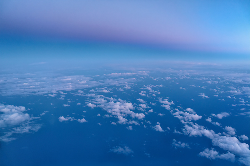 Clouds over pacific ocean with sunset. Shot from airplane.