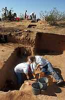 UA student Erin Coward (left) and Dean Duryea, a .University of Arizona senior.students shovels dirt to be screened of dirt from.the Marana Platform mound looking for.shards and other artifacts from the .mound occupied for 100 years by the HoHoKam.people from 1200 ad to 1300 ad.....in this picture the students are evacuating.a room 40x40 in size, they have divided it up into.four sections and are working one quarter at a time...