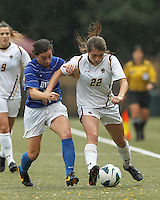 Boston College defender McKenzie Meehan (22) dribbles down the wing as Duke University defender Christina Gibbons (31) pressures.Boston College (white) defeated Duke University (blue/white), 4-1, at Newton Campus Field, on October 6, 2013.