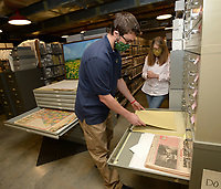 Aaron Loehndorf (left), collections and education specialist at the Shiloh Museum of Ozark History, and Carolyn Reno, collections manager, arrange pieces of the museum's collection Thursday, Sept. 10, 2020, into a drawer while reorganizing and consolidating the museum's collection at the museum in Springdale. The museum is open to all visitors 10 a.m. to 5 p.m. with limitations and pandemic-related expectations in place. Thursday mornings from 10 a.m. to noon are reserved for high-risk visitors only. Visit nwaonline.com/200913Daily/ for today's photo gallery. <br /> (NWA Democrat-Gazette/Andy Shupe)