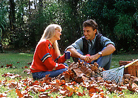 A smiling couple laughs and talks while taking a break from raking leaves in their yard.