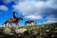 """Rowan, a five-year-old autistic child, riding a horse, accompanied by his parents, Kristin Neff and Rupert Issacson, during a horseback expedition across Mongolia. Rowan, who has been nicknamed """"The Horse Boy"""", embarked on a therapeutic journey of discovery with his parents to visit a succession of shaman healers in one of the most remote regions in the world. Following Rowan's positive response to a neighbour's horse, Betsy, and some reaction to treatment by healers, Rowan's parents hoped that the Mongolian shamanistic rituals along the route and the prolonged contact with horses would help to unlock their son's autism and assist his development.."""