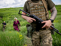 Natalia Voronkova, a volunteer who offers support and basic first aid training for Ukrainian government forces fighting Russian-backed separatists in the east of the country, walks with soldiers near frontline positions. The situation is tense here, with mortar attacks and snipers ready to fire at their next target if the soldiers do not stay under cover.<br /><br />Natalia Voronkova says she hasn't worn jeans since 2014, and it's a statement for her to insist on wearing long dresses and high heels, even while walking in the trenches. She believes that her clear civilian appearance will protect her from snipers, but she also thinks that it brings a message of normality to the Ukrainian soldiers. It encourages them to not give up, if she can walk here in such clothes they might also find the strength to carry on under such hard living conditions.