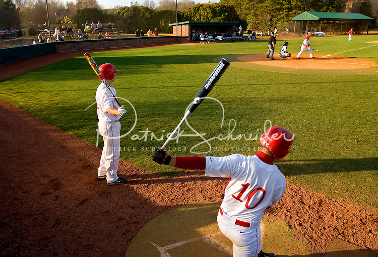 A baseball player warms up in the on deck circle waiting to hit.