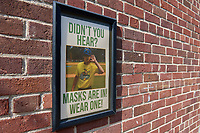 A sign in the stadium walkway to remind fans to wear a mask before a Collegiate Summer League game  between the Macon Bacon and Savannah Bananas on July 15, 2020 at Grayson Stadium in Savannah, Georgia.  (Mike Janes/Four Seam Images)
