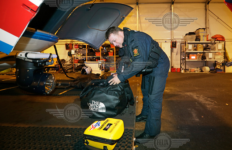 Norwegian Police Helicopter. System operator Lasse Iversen checking kit in the helicopter before a mission.