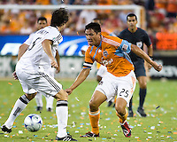 Houston Dynamo forward Brian Ching (25) attempts to dribble through D.C. United defender Dejan Jakovic (5).  Houston Dynamo defeated D.C. United 4-3 at Robertson Stadium in Houston, TX on August 1, 2009.