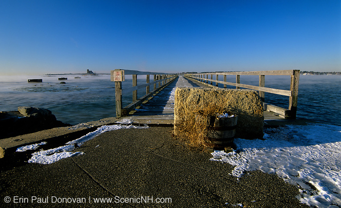 Long wooden wharf / pier at Fort Foster, which is an old fort located in Kittery, Maine USA, in Portsmouth Harbor. Wood Island Lifesaving Station can be seen off to the left.