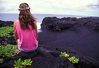 Woman sitting on lava rock near black sand beach. Hawaii Volcanoes National Park, Big Island