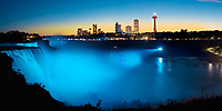 Amazing Niagara Falls panorama with water lit up in blue under a clear blue and orange sky, USA and Canada