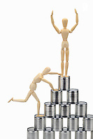 Wooden mannequin climbing tin cans pyramid (Licence this image exclusively with Getty: http://www.gettyimages.com/detail/102918624 )