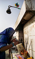 Delhi / India.Fedele di religione indu con altare votivo nei pressi delle rive del fiume Yamuna.Foto Livio Senigalliesi.Delhi / India.Faithful of Hindu religion praying near votive altar along the banks of the river Yamuna..Photo Livio Senigalliesi.