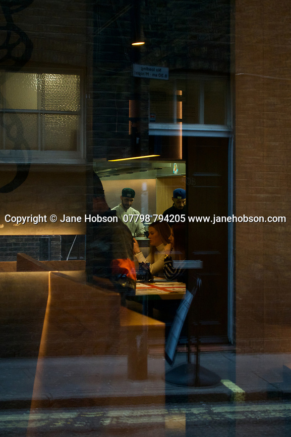 London, UK. 02.02.2020. Inside/outside - reflections in, and view through, a restaurant window, Soho, London, UK. Photograph © Jane Hobson.